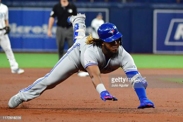 Vladimir Guerrero Jr #27 of the Toronto Blue Jays slides to third after hitting a triple off of Austin Pruitt of the Tampa Bay Rays in the first...