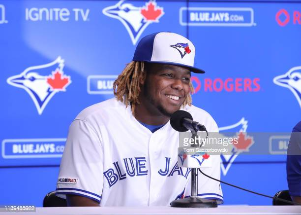 Vladimir Guerrero Jr #27 of the Toronto Blue Jays smiles as he speaks to the media through an interpreter as he is introduced before his MLB debut...