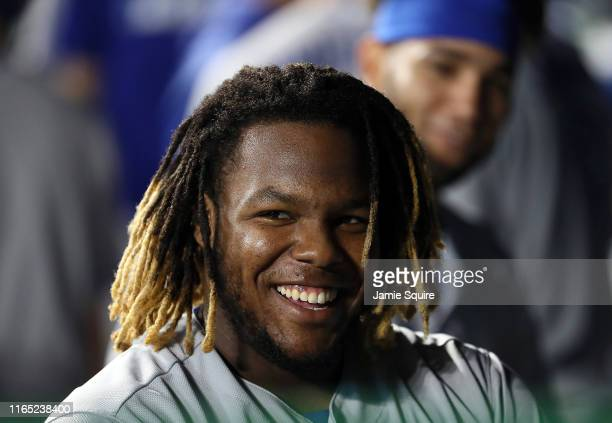 Vladimir Guerrero Jr. #27 of the Toronto Blue Jays smiles in the dugout after hitting a grand slam home run during the 9th inning of the game against...