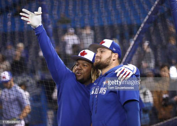 Vladimir Guerrero Jr #27 of the Toronto Blue Jays talks to Rowdy Tellez during batting practice before the start of MLB game action against the...