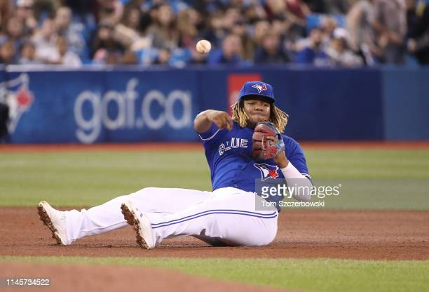 Vladimir Guerrero Jr #27 of the Toronto Blue Jays throws from the seat of his pants to get the baserunner at first base as he falls after fielding a...