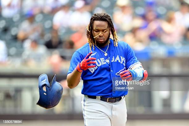 Vladimir Guerrero Jr. #27 of the Toronto Blue Jays tosses his helmet after flying out against the New York Mets during the third inning at Citi Field...