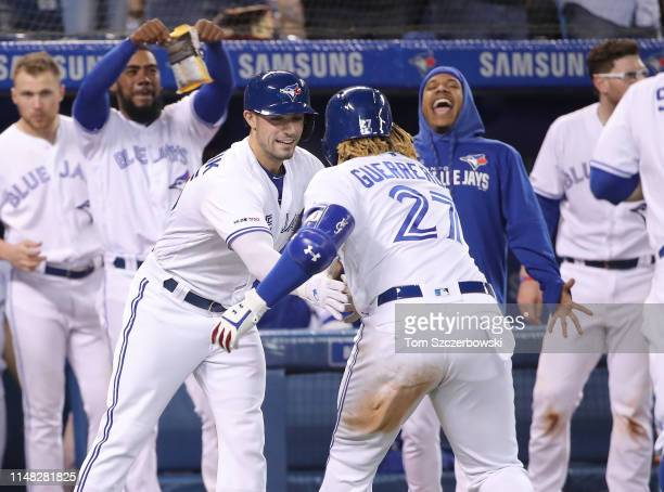 Vladimir Guerrero Jr #57 of the Toronto Blue Jays is congratulated by Randal Grichuk after hitting a threerun home run in the eighth inning during...
