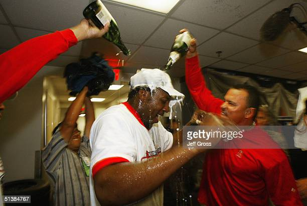 Vladimir Guerrero of the Anaheim Angels gets a champagne shower from coach Orlando Mercado following the Angels 54 victory over the Oakland A's to...