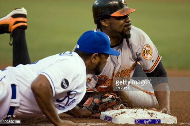 Vladimir Guerrero of the Baltimore Orioles slides safely into third past the tag of Yamaico Navarro of the Kansas City Royals as he advances on Mark...