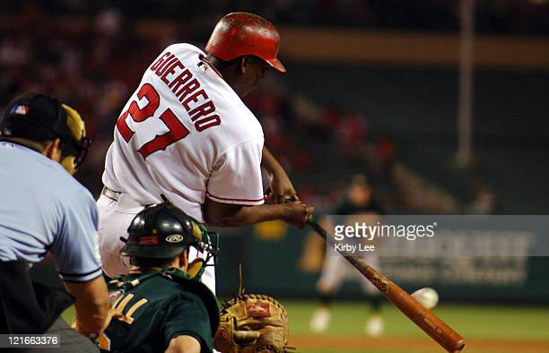 Vladimir Guerrero of the Los Angeles Angels of Anaheim bats as Oakland Athletics catcher Jason Kendall and home plate umpire Chris Guccione watch The...
