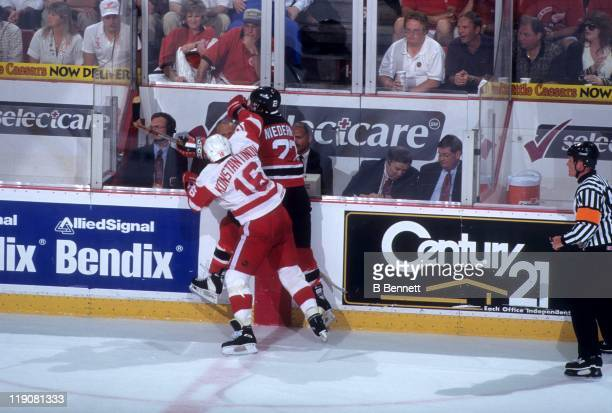 Vladimir Konstantinov of the Detroit Red Wings checks Scott Niedermayer of the New Jersey Devils into the boards during Game 2 of the 1995 Stanley...