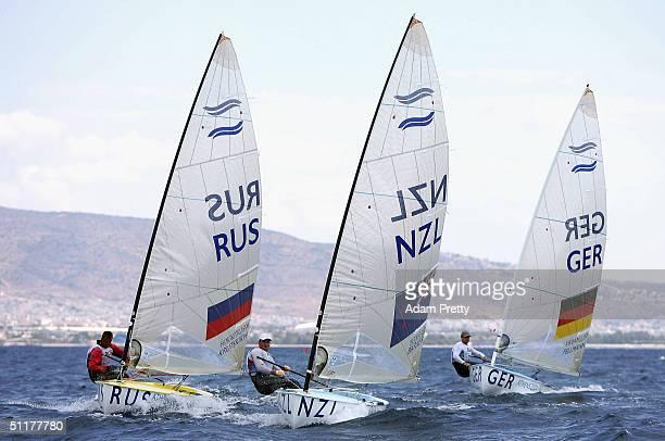 Vladimir Krutskikh of Russia Dean Barker of New Zealand and Michael Fellmann of Germnay race in the men's single handed dinghy finn race on August 16...
