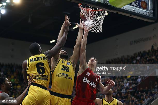 Vladimir Lucic of Muenchen is challenged by Johannes Thiemann and Kelvin Martin of Ludwigsburg during the easyCredit BBL match between MHP Riesen...