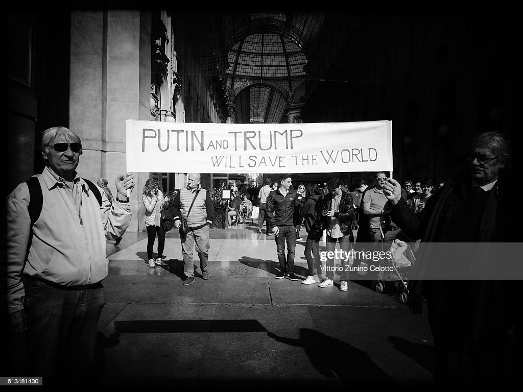 Image has been converted to black and white.) Vladimir Putin and Donald Trump supporters are seen on October 7, 2016 in Milan, Italy.