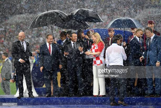 Vladimir Putin President of Russia Emmanuel Macron President of France and Kolinda GrabarKitarovic President of Croatia reacts to the rain while they...