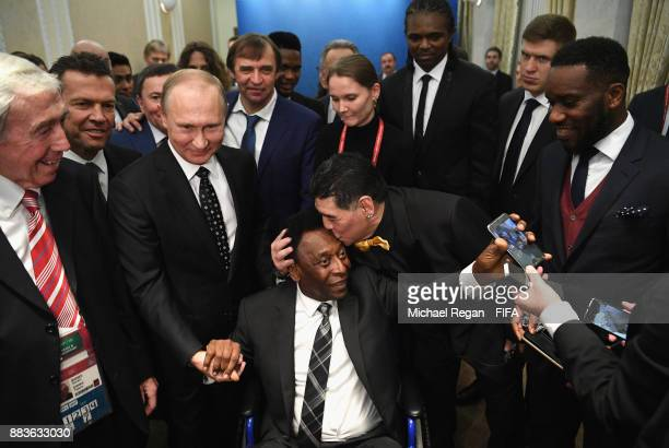 Vladimir Putin, President of Russia shakes hands with Pele as Draw assistant, Diego Maradona kisses his head prior to the Final Draw for the 2018...