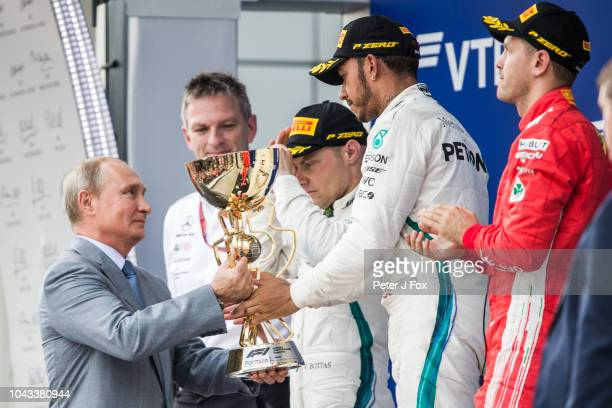 Vladimir Putin Russian President presents Lewis Hamilton of Mercedes and Great Britain with the winners trophy during the Formula One Grand Prix of...