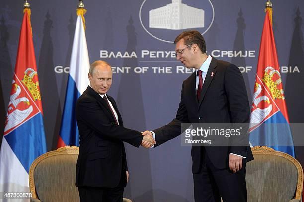 Vladimir Putin Russia's president left and Aleksandar Vucic Serbia's prime minister shake hands ahead of their meeting in Belgrade Serbia on Thursday...