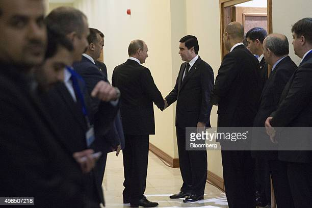 Vladimir Putin Russia's president left shakes hands with Gurbanguly Berdimuhamedow Turkmenistan's president in the corridor after a news conference...