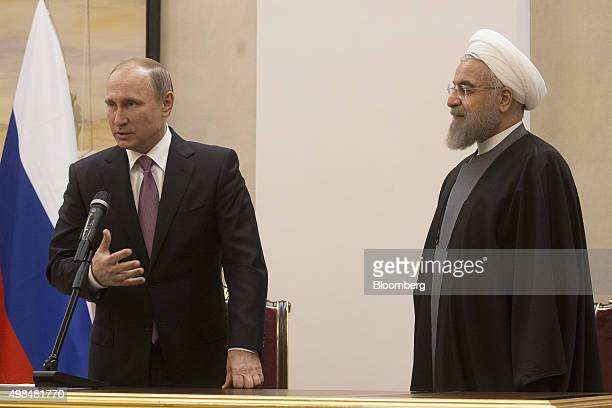 Vladimir Putin Russia's president left speaks as Hassan Rouhani Iran's president listens during a news conference at the Gas Exporting Countries...