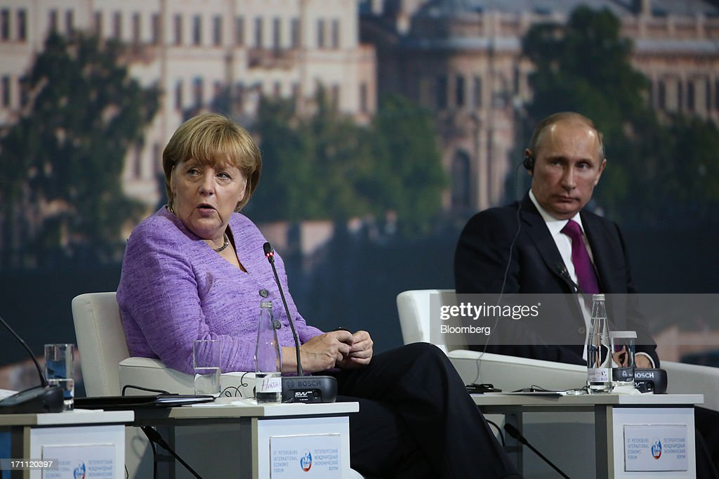 Vladimir Putin, Russia's president, right, looks on while Angela Merkel, Germany's chancellor, speaks during a session on day two of the St. Petersburg International Economic Forum 2013 (SPIEF) in St. Petersburg, Russia, on Friday, June 21, 2013. Putin is battling investor skepticism to woo foreign executives descending on his hometown today as Russia's economy faces a risk of recession and a crackdown on critics scares off intellectuals. Photographer: Andrey Rudakov/Bloomberg via Getty Images