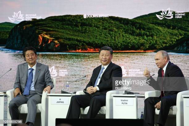 Vladimir Putin Russia's president right speaks as Shinzo Abe Japan's prime minister left and Xi Jinping China's president look on during day two of...