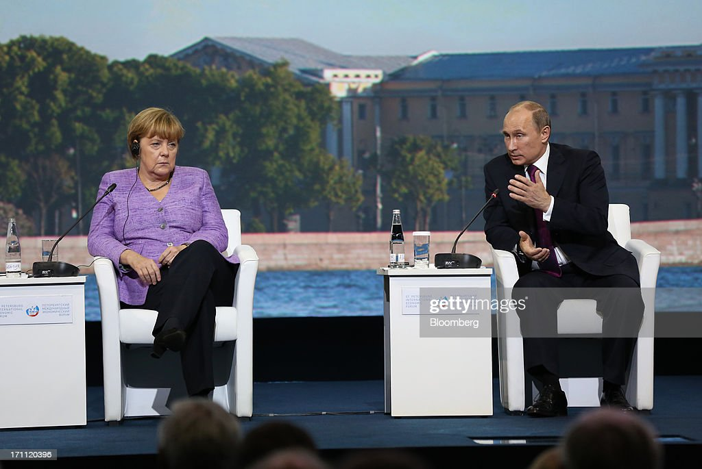 Vladimir Putin, Russia's president, right, speaks while Angela Merkel, Germany's chancellor, looks on during a session on day two of the St. Petersburg International Economic Forum 2013 (SPIEF) in St. Petersburg, Russia, on Friday, June 21, 2013. Putin is battling investor skepticism to woo foreign executives descending on his hometown today as Russia's economy faces a risk of recession and a crackdown on critics scares off intellectuals. Photographer: Andrey Rudakov/Bloomberg via Getty Images