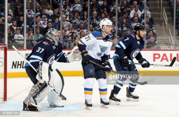 Vladimir Sobotka of the St Louis Blues stands between goaltender Connor Hellebuyck and Ben Chiarot of the Winnipeg Jets as they keep an eye on the...