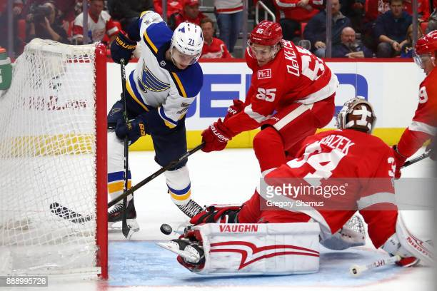 Vladimir Sobotka of the St Louis Blues tries to get a third period shot off next to Petr Mrazek and Danny DeKeyser of the Detroit Red Wings at Little...