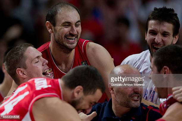 Vladimir Stimac of Serbia celebrates embraced with his teammate Nenad Krstic their victory against France with their teammates and head coach Sasha...