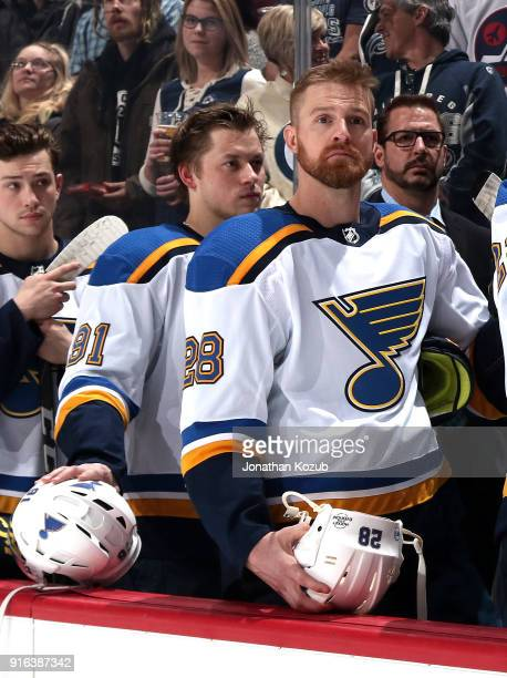 Vladimir Tarasenko and Kyle Brodziak of the St Louis Blues look on from the bench during the singing of the National anthems prior to puck drop...