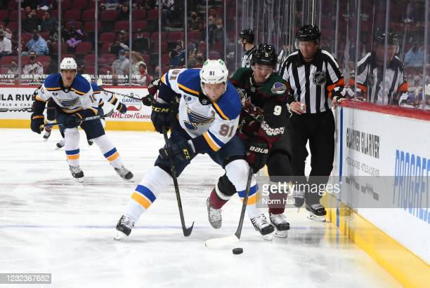 Vladimir Tarasenko of the St Louis Blues and Clayton Keller of the Arizona Coyotes battle for control of the puck along the boards during the first...