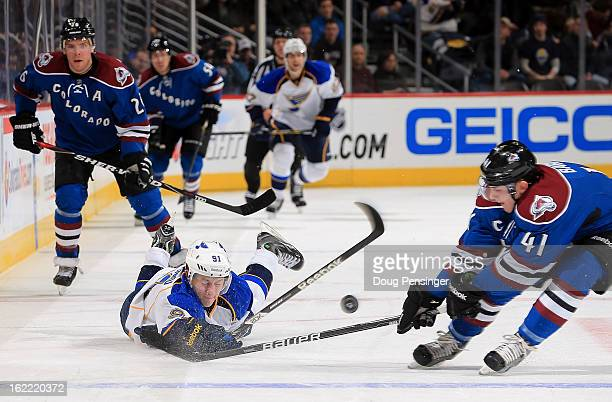 Vladimir Tarasenko of the St Louis Blues dives to move the puck over the blue line against Tyson Barrie of the Colorado Avalanche at the Pepsi Center...