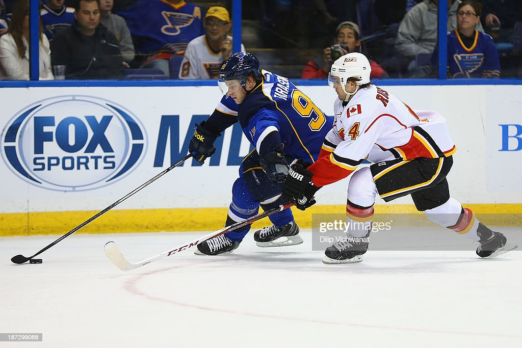 Vladimir Tarasenko #91 of the St. Louis Blues fends off Kris Russell #4 of the Calgary Flames as he controls the puck at the Scottrade Center on November 7, 2013 in St. Louis, Missouri. The Blues beat the Flames 3-2.