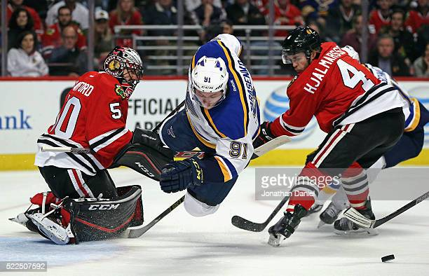 Vladimir Tarasenko of the St Louis Blues goes airborne trying to get off a shot between Corey Crawford and Niklas Hjalmarsson of the Chicago...