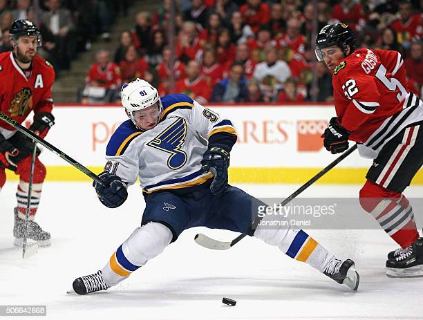 Vladimir Tarasenko of the St Louis Blues loses his balance skating between Brent Seabrook and Erik Gustafsson of the Chicago Blackhawks at the United...