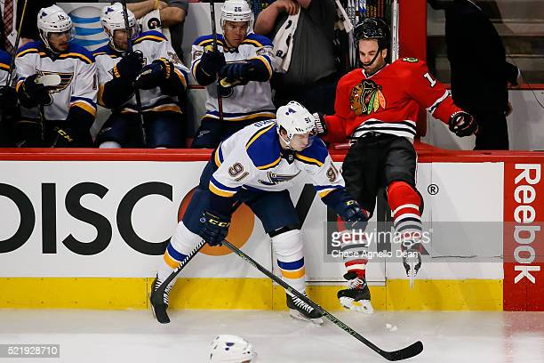 Vladimir Tarasenko of the St Louis Blues pushes Andrew Ladd of the Chicago Blackhawks into the boards in the first period of Game Three of the...
