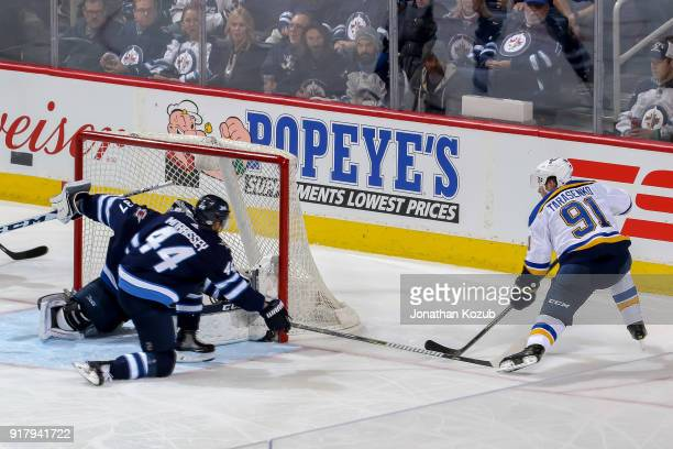 Vladimir Tarasenko of the St Louis Blues shoots the puck past a defending Josh Morrissey and goaltender Connor Hellebuyck of the Winnipeg Jets for a...