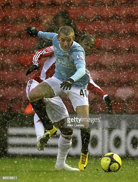 Vladimir Weiss of Manchester City tangles with Justin Hoyte of Middlesbrough as snow falls during the FA Cup sponsored by EON 3rd Round match between...
