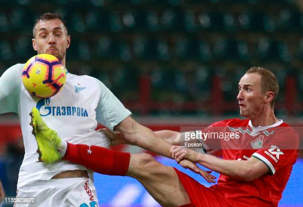 Vladislav Ignatyev of FC Lokomotiv Moscow is challenged by Artem Dzyuba of FC Zenit Saint Petersburg during the Russian Premier League match between...