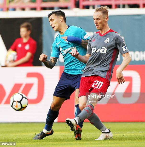 Vladislav Ignatyev of FC Lokomotiv Moscow vie for the ball with Leandro Paredes of FC Zenit Saint Petersburg during the Russian Football League match...