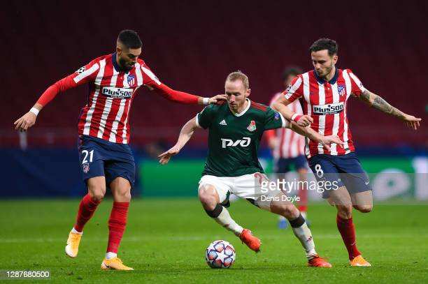 Vladislav Ignatyev of Lokomotiv Moscow is challenged by Yannick Ferreira Carrasco and Saul Niguez of Atletico de Madrid during the UEFA Champions...