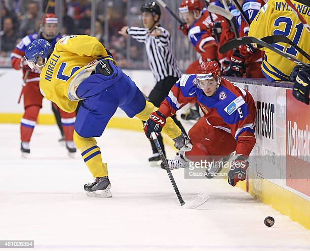 Vladislav Kamenev of Team Russia is taken down by Robin Norell of Team Sweden during a semifinal game in the IIHF World Junior Hockey Championship at...