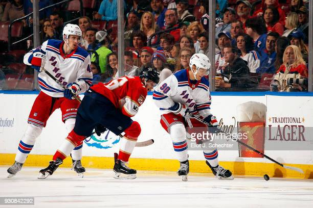 Vladislav Namestnikov and Rob O'Gara of the New York Rangers tangle with Maxim Mamin of the Florida Panthers at the BBT Center on March 10 2018 in...