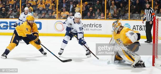 Vladislav Namestnikov of the Tampa Bay Lightning shoots the puck against Pekka Rinne and Ryan Ellis of the Nashville Predators during an NHL game at...