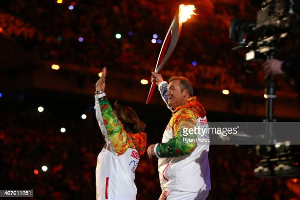 Vladislav Tretyak carries the Olympic torch with Irina Rodina during the Opening Ceremony of the Sochi 2014 Winter Olympics at Fisht Olympic Stadium...