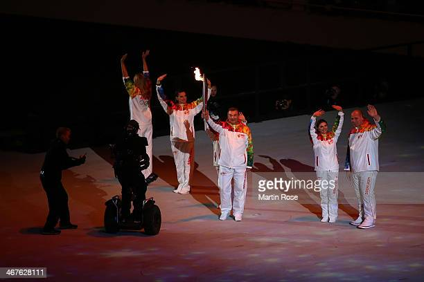 Vladislav Tretyak holds up the Olympic torch as Maria Sharapova Elena Isinbaeva Alina Kabaeva and Alexandr Karelin wave during the Opening Ceremony...