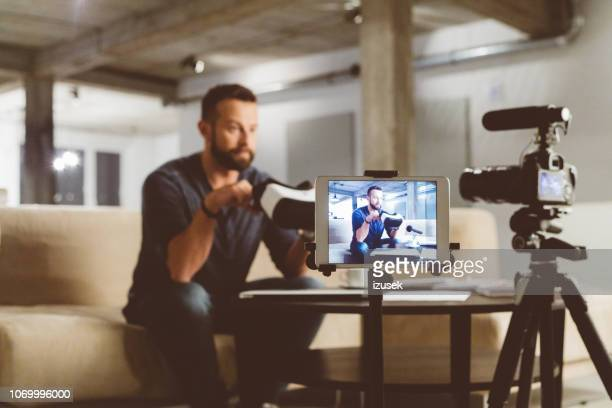 vlogger reviewing vr goggles in vlog - vlogging stock photos and pictures