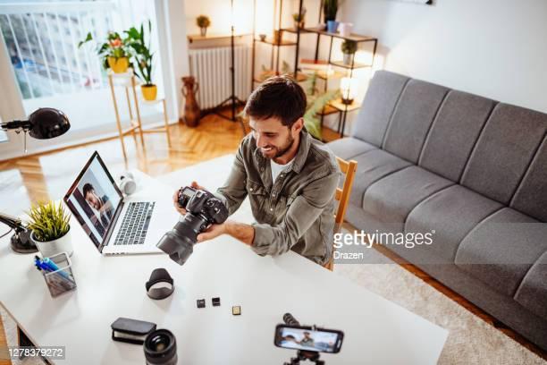 vlogger test nieuwe camera en lens - mens die zich in woonkamer registreert - fotograaf stockfoto's en -beelden