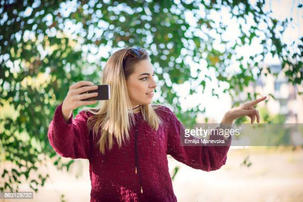 Vlogging concept. Young beautiful fashionable woman making a video for her blog with mobile phone