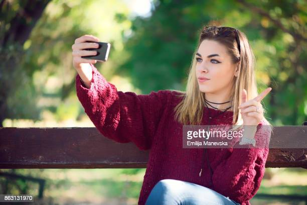 vlogging concept. young beautiful fashionable woman making a video for her blog with mobile phone - vlogging stock photos and pictures