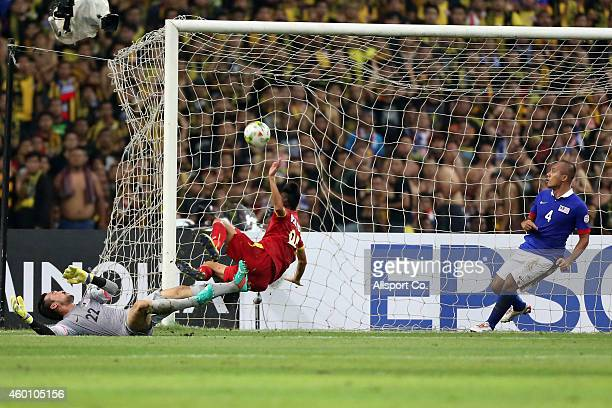 Vo Huy Toan of Vietnam scores against Khairul Fahmi of Malaysia during the 2014 AFF Suzuki Cup semi final 1st leg match between Malaysia and Vietnam...