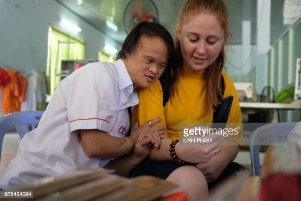 Vo Nhat Truyen who suffer from the affects of Agent Orange leans on the shoulder of a US Navy sailor during a visit by the crew of USS Carl Vinson in...