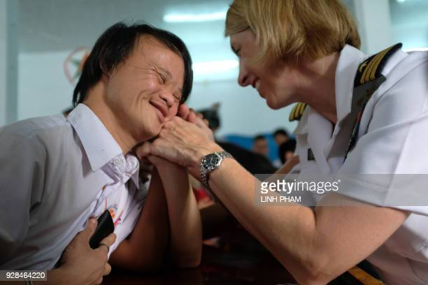 Vo Nhat Truyen who suffers the affects of Agent Orange interacts with a US Navy sailor at a centre for victims of the wartime defoliant during a...